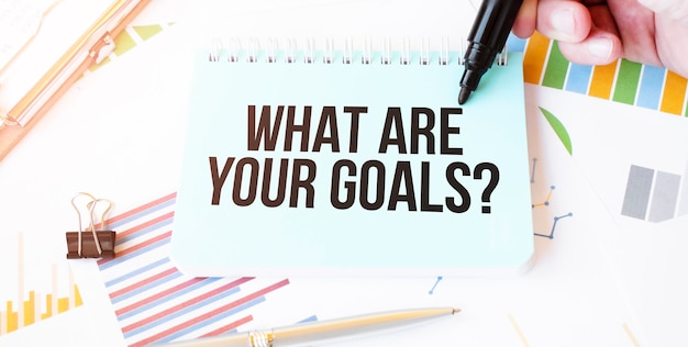 Mano de hombre de negocios, plato de papel, marcador, diagrama, gráfico y herramientas de oficina. texto ¿cuáles son tus objetivos?