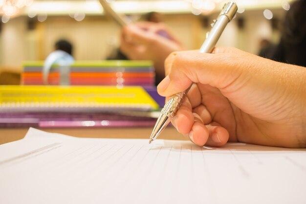 Mano de hombre de negocios con pluma de plata para tomar notas en papeleo blanco o documento