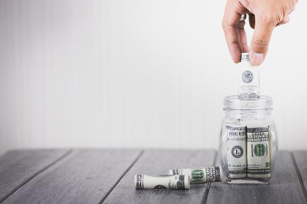 Mano de hombre de negocios poniendo dinero cien dólares en botella de vidrio, ahorrar dinero, negocios