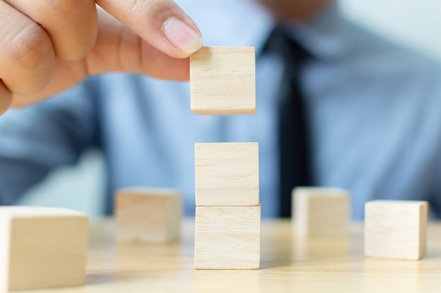 Mano del hombre de negocios que arregla el bloque de madera que apila en el top con la tabla de madera.