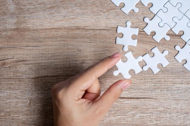 Mano de hombre de negocios que conecta la pieza del rompecabezas. soluciones comerciales, objetivo de misión