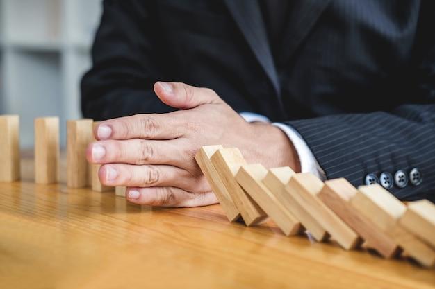 Mano de hombre de negocios que detiene el efecto dominó de madera que cae de continuo derribado o riesgo