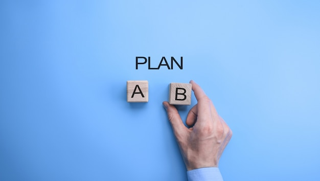 Mano de hombre de negocios que elige la opción del plan b. vista superior sobre fondo azul