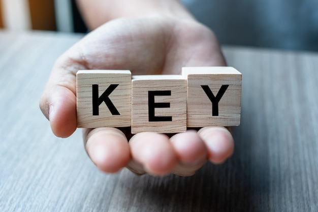 Mano del hombre de negocios que lleva a cabo el bloque de madera del cubo con palabra clave del negocio en fondo de la tabla.