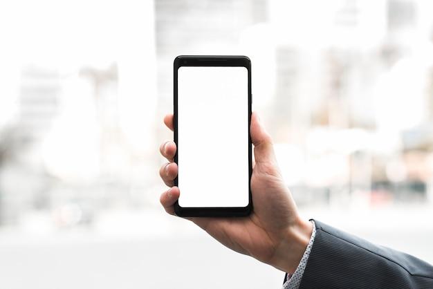 La mano de un hombre de negocios que muestra el teléfono móvil contra fondo borroso