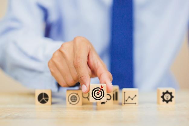 Mano del hombre de negocios que pone el bloque de madera del cubo en el top con concepto del éxito de la blanco.
