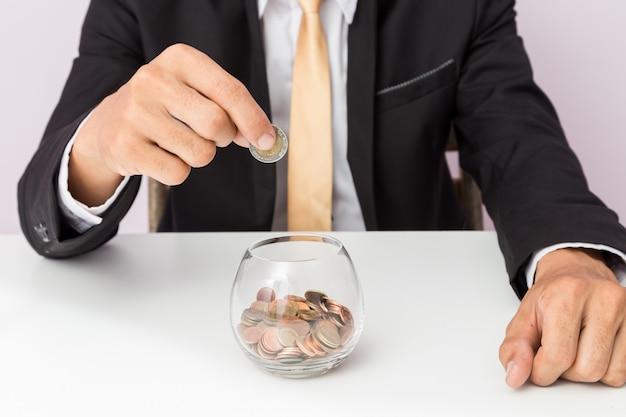 Mano del hombre de negocios que pone las monedas en el vidrio, concepto de ahorrar el dinero para la contabilidad de las finanzas