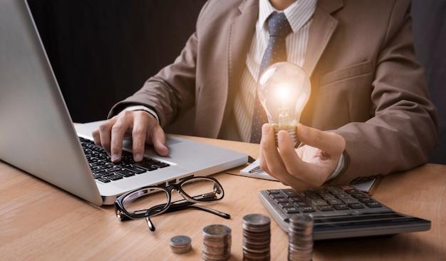 Mano de hombre de negocios que sostiene la bombilla con usar la calculadora para calcular