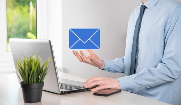 Mano de hombre de negocios que sostiene el icono de correo electrónico, contáctenos por correo electrónico del boletín y proteja su información personal del correo no deseado. centro de llamadas de servicio al cliente contáctenos concepto.