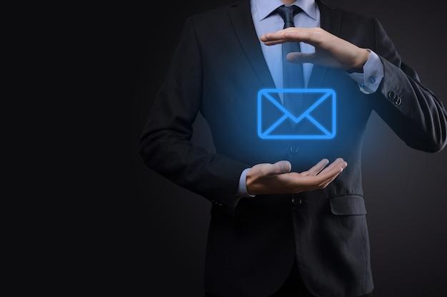Mano de hombre de negocios que sostiene el icono de correo electrónico, contáctenos por correo electrónico del boletín y proteja su información personal del correo no deseado. centro de llamadas de servicio al cliente en contacto con nosotros concepto.