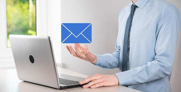 Mano de hombre de negocios que sostiene el icono de correo electrónico, contáctenos por correo electrónico del boletín y proteja su información personal del correo no deseado. centro de llamadas de servicio al cliente, póngase en contacto con nosotros concepto