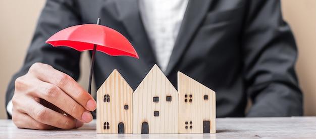Mano de hombre de negocios que sostiene el modelo casero de madera de la cubierta del paraguas rojo en la oficina de la mesa.