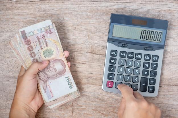 Mano del hombre de negocios que sostiene la pila del billete de banco del baht tailandés y que usa la calculadora.