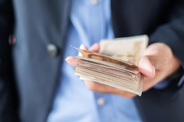 Mano del hombre de negocios que sostiene la pila del billete de banco del baht tailandés.