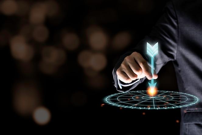 Mano del hombre de negocios que sostiene y que lanza el dardo virtual para apuntar al tablero en la pared negra. Concepto del objetivo del negocio y de la inversión.