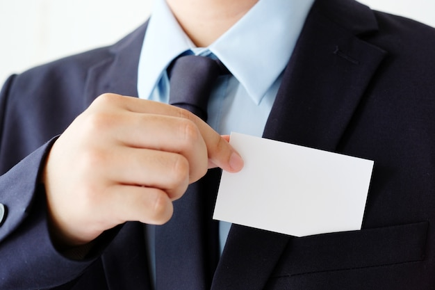 Mano de hombre de negocios que sostiene la tarjeta de visita blanca en blanco con el espacio de la copia para el texto