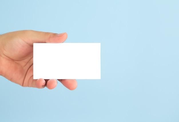 Mano de hombre de negocios que sostiene la tarjeta de visita en blanco sobre fondo azul claro.