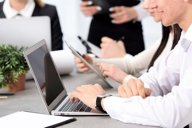 La mano del hombre de negocios sonriente usando el ordenador portátil que se sienta con su colega en el escritorio