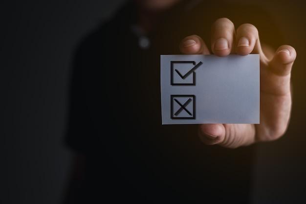 La mano del hombre de negocios sosteniendo el libro blanco con cheque de elección, concepto de negocio y oficina de encuesta, luz naranja gráfica de computadora, icono de cheque