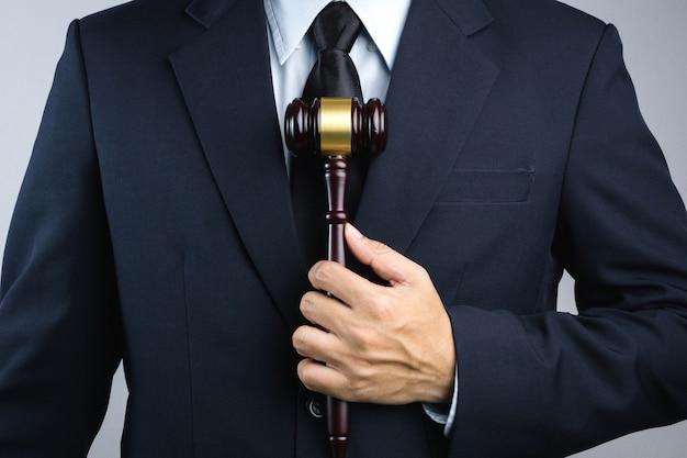 Mano de hombre de negocios sosteniendo el mazo del juez de madera como una ley o signo de la justicia