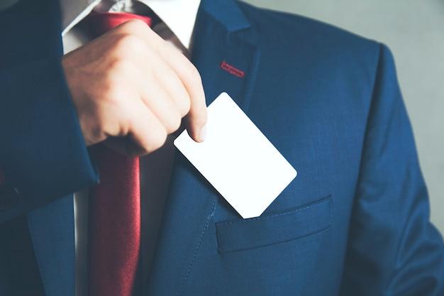 Mano de hombre de negocios sosteniendo una tarjeta de visita sobre el bolsillo del traje
