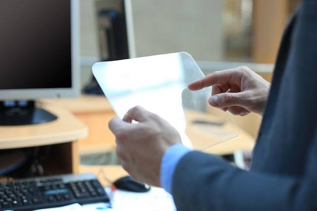 Mano de hombre de negocios con tableta transparente y computadora pc.