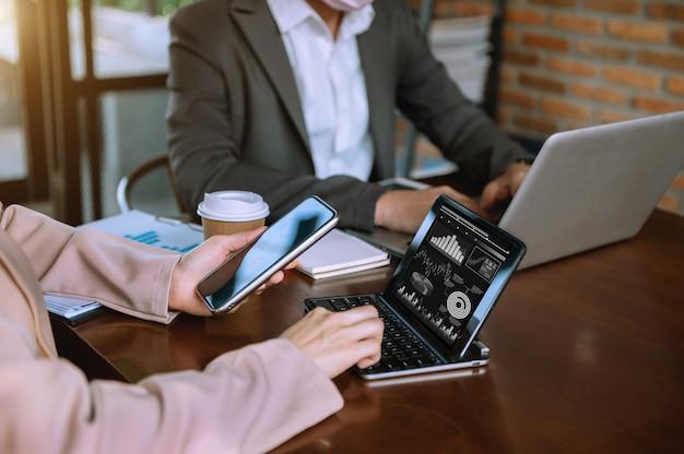 Mano de hombre de negocios con teléfono inteligente, computadora portátil y tableta con diagrama de red social y dos colegas discutiendo datos sobre el escritorio como concepto a la luz de la mañana.