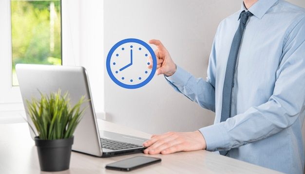 Mano de hombre de negocios tiene el icono del reloj de horas con flecha. rápida ejecución de la obra. tiempo laboral.