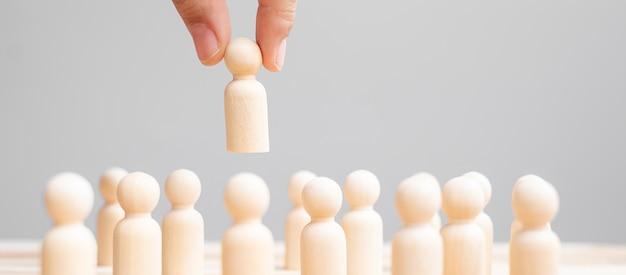 Mano de hombre de negocios tirando al hombre líder de madera de la multitud de empleados. conceptos de personas tóxicas, gestión de recursos humanos, contratación, trabajo en equipo y liderazgo