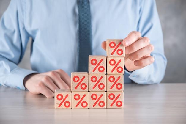La mano del hombre de negocios toma un bloque de cubo de madera que representa el icono del símbolo de porcentaje.