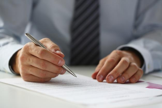 Mano de hombre de negocios en traje de relleno y firma con