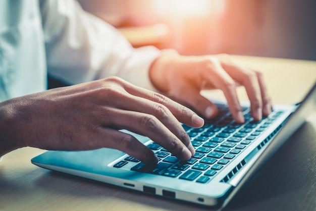 Mano de hombre de negocios usando la computadora portátil en la oficina.