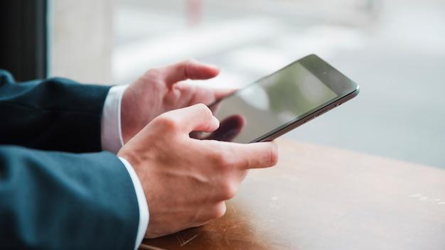 La mano del hombre de negocios usando teléfono inteligente en café