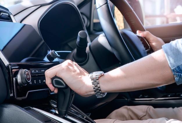 Mano de hombre con niveles de palanca de cambios. mano del hombre del conductor que lleva a cabo la transmisión automática en coche.