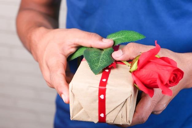 Mano de hombre no reconocido sosteniendo una flor color de rosa y una caja de regalo de cerca.