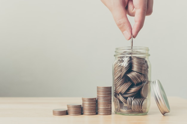 Mano de hombre o mujer poniendo monedas en el tarro con dinero