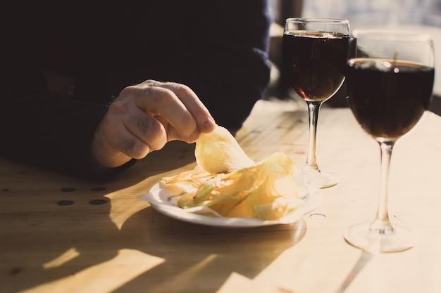 Una mano de hombre con una papa de papas fritas y dos vasos de vermout. aperitivo español