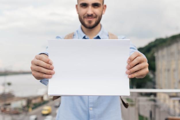 La mano del hombre con papel blanco en blanco