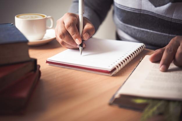 La mano de un hombre con una pluma y tomar notas en un cuaderno.