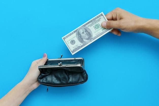 Mano de hombre poniendo billete de cien dólares en el bolso en la mano de la mujer. concepto de crisis financiera. foto de alta calidad