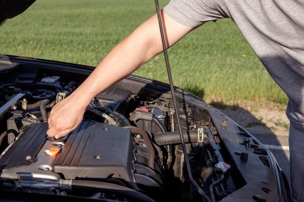 Mano del hombre, preparando para agregar un poco de aceite en el motor durante el viaje en una carretera