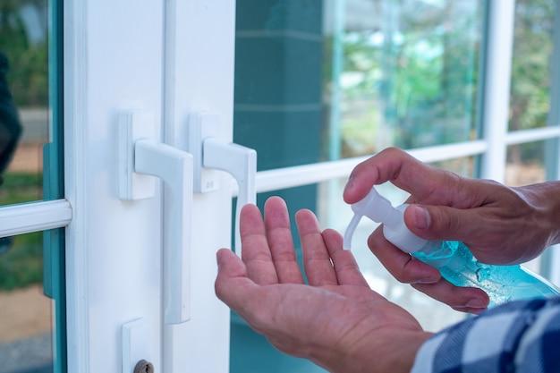La mano del hombre presiona el gel para lavarse las manos y matar gérmenes antes de entrar y salir o atrapar puertas. concepto de limpieza e higiene. prevención de covid-19