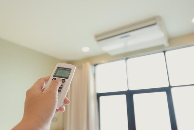 La mano de un hombre está presionando el control remoto del aire acondicionado en su mano para descansar
