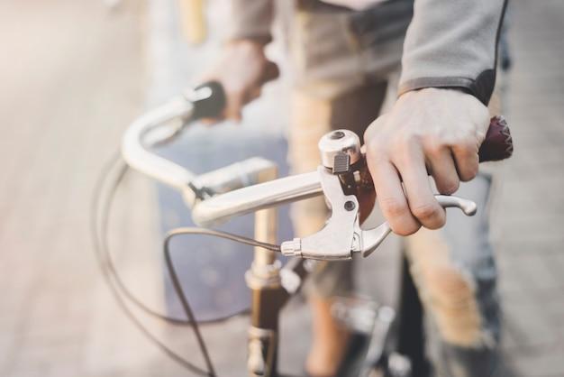 La mano del hombre presionando el freno de la bicicleta