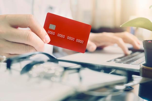 Mano del hombre del primer que sostiene la tarjeta de crédito roja mientras que se sienta en el escritorio de oficina en oficina moderna.