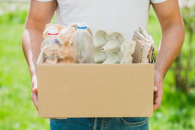 Mano del hombre con productos de reciclaje en la caja de cartón.