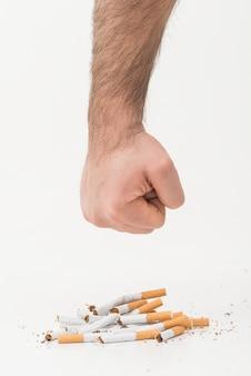 Mano de un hombre que da un puñetazo a los cigarrillos rotos aislados sobre fondo blanco