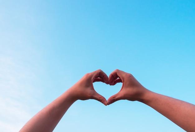 La mano del hombre que hace la forma del corazón ama el cielo azul.