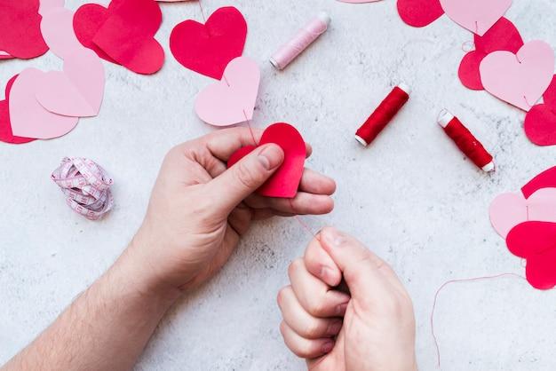 La mano del hombre que hace la guirnalda de papel roja y rosada de la forma del corazón con el hilo en el fondo blanco