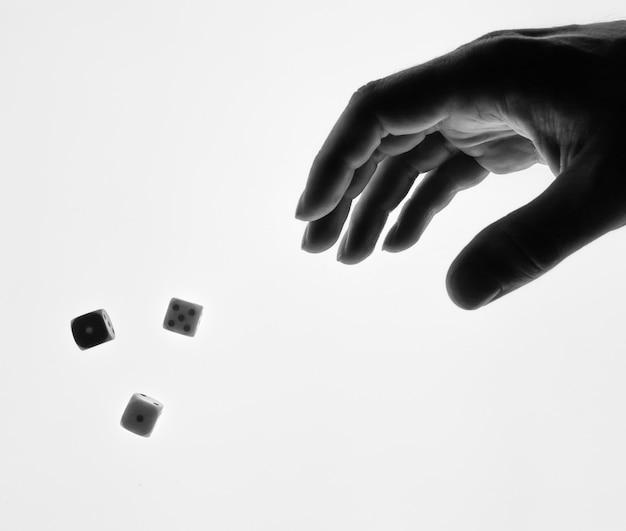 La mano del hombre que lanza la silueta blanco y negro de los dados aislada.